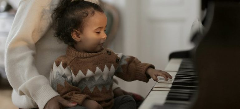 Toddler playing a piano after it was moved with piano movers Ottawa