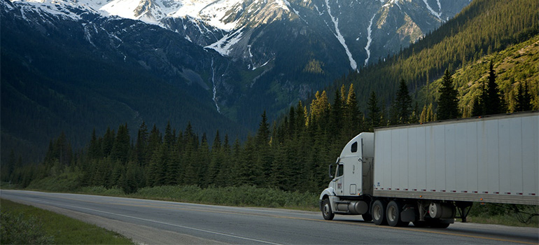 A truck on a clear highway with mountains in the background